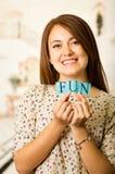 Femme avec du charme de brune de Headshot retardant les minuscules orthographiant l'amusement de mot et souriant à l'appareil-pho Image stock