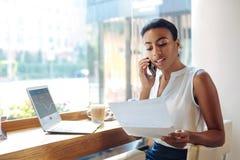 Femme avec du charme discutant des résultats de la recherche au téléphone Image stock