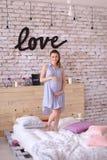 Femme avec du charme enceinte portant la robe bleue tenant le ventre, amour d'inscription sur le mur de briques Photos stock