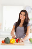 Femme avec du charme faisant cuire des légumes tout en restant Image stock