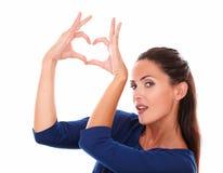 Femme avec du charme faisant un signe d'amour Photos libres de droits