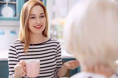 Femme avec du charme parlant à sa mère dans la cuisine Photographie stock