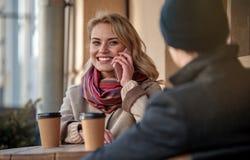Femme avec du charme parlant au téléphone tout en regardant l'homme Image stock