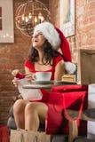 Femme avec du charme portant le cadeau de Noël d'ouverture de chapeau de Santa Claus Image stock