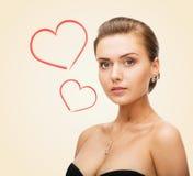 Femme avec du charme utilisant les boucles d'oreille brillantes de diamant Photos stock