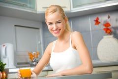 Femme avec du jus à la cuisine images libres de droits