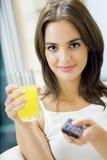 Femme avec du jus, TV de observation photos stock