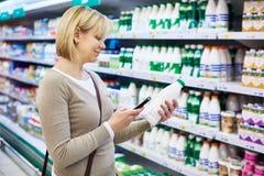 Femme avec du lait d'achats de téléphone portable Photos stock