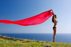 Femme avec du matériau et la nature rouges Images stock