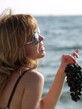 Femme avec du raisin sur la plage Images stock