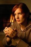 Femme avec du thé (cheminée derrière) Images stock
