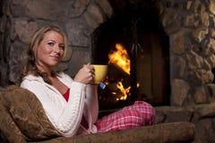 Femme avec du thé se reposant par Fireplace Photographie stock libre de droits