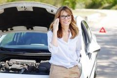 Femme avec elle véhicule décomposé photographie stock