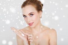 Femme avec hydrater la crème en main au-dessus de la neige images stock