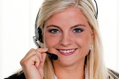 Femme avec l'écouteur de téléphone à un centre d'attention téléphonique Images stock