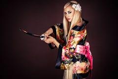 Femme avec l'épée samouraï d'isolement sur le brun Photo stock