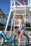Femme avec l'équitation de bicyclette sur le sable de plage ayant l'amusement et le sourire photos libres de droits