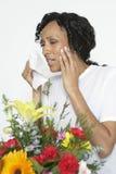 Femme avec l'allergie tenant le tissu près des fleurs image stock