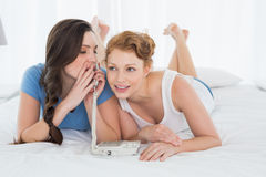 Femme avec l'ami à l'aide du téléphone tout en se trouvant dans le lit Photographie stock libre de droits