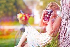 Femme avec l'appareil-photo détendant après tour de bicyclette Image stock