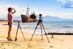 Femme avec l'appareil-photo sur le trépied et le naufrage photographie stock