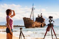 Femme avec l'appareil-photo sur le trépied et le naufrage images libres de droits