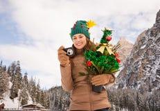 Femme avec l'arbre de Noël vérifiant la photo devant montagnes Photos stock