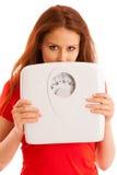 Femme avec l'échelle peu satisfaite de son poids faisant des gestes la tristesse et le W Image stock