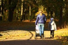 Femme avec l'enfant de voiture landau et d'aîné en parc Photographie stock