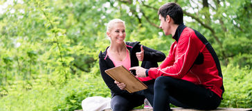 Femme avec l'entraîneur personnel à l'évaluation courante photo libre de droits