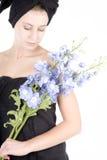 Femme avec l'essuie-main autour des fleurs de fixation de cheveu Photographie stock libre de droits