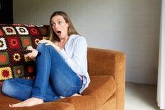 Femme avec l'expression étonnée de visage regardant la TV photographie stock libre de droits