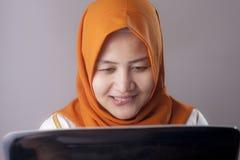 Femme avec l'expression vilaine regardant l'ordinateur portable photos stock