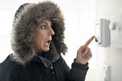 Femme avec l'habillement chaud sentant le froid à l'intérieur de la Chambre photo stock