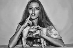 Femme avec l'hamburger et le pigglet Photographie stock