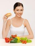 Femme avec l'hamburger et les légumes Photographie stock libre de droits