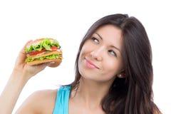 Femme avec l'hamburger malsain savoureux d'aliments de préparation rapide à disposition à manger Photo libre de droits