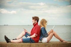 Femme avec l'homme de smartphone avec des couples de comprimé extérieurs Photo libre de droits