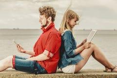 Femme avec l'homme de smartphone avec des couples de comprimé extérieurs Photos libres de droits