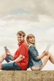 Femme avec l'homme de smartphone avec des couples de comprimé extérieurs Photo stock