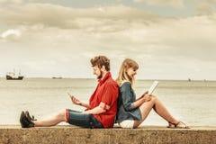 Femme avec l'homme de smartphone avec des couples de comprimé extérieurs Images stock