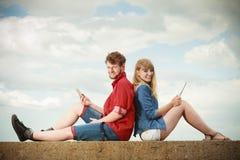 Femme avec l'homme de smartphone avec des couples de comprimé extérieurs Image libre de droits