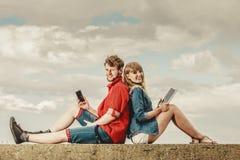Femme avec l'homme de smartphone avec des couples de comprimé extérieurs Photographie stock libre de droits