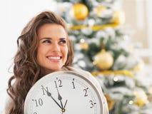 Femme avec l'horloge regardant sur l'espace de copie dans l'arbre de Noël de frontof Photos stock