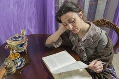 Femme avec l'intention de châle sur la lecture Photographie stock