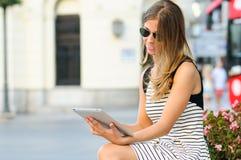 Femme avec l'ordinateur de tablette à l'arrière-plan urbain Photo stock