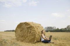 Femme avec l'ordinateur portable contre Hay Bale In Field Photo stock