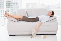 Femme avec l'ordinateur portable dormant sur le sofa à la maison Photos stock