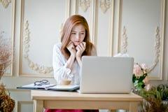Femme avec l'ordinateur portable observant le film triste Image stock