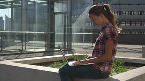 Femme avec l'ordinateur portable près de la façade en verre banque de vidéos